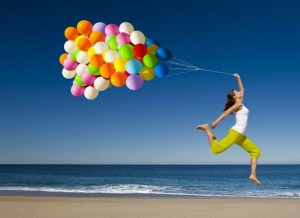 Woman at Beach Jumping with Balloons